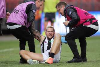 Jeremy Howe is helped up by Collingwood trainers after his final-term clash with Jacob Hopper.