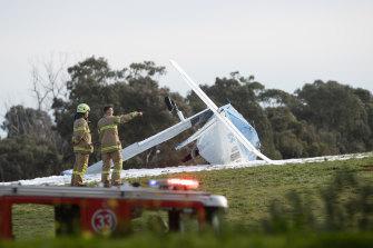 Firefighters inspect the crash scene near Moorabbin Airport on Tuesday.