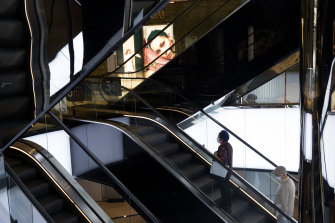 A couple of people in masks ride the escalator in a nearly deserted Westfield in Sydney.