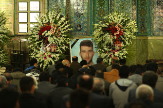 Men gather in front of a large photo of killed asylum seeker Reza Berati during the memorial service, held at the Al-Mahdi mosque in the Nabard neighbourhood in South East Tehran, Iran.