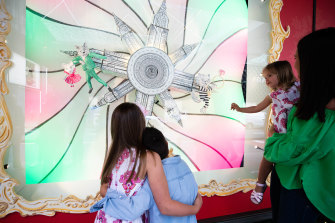 Emily Smith with her children, Charlotte, 8, Louis, 5, and Amelia, 3, looking at David Jones Christmas windows in Sydney.