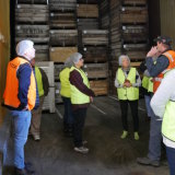A tour group visits an apple packing shed.