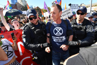 Police arrest an Extinction Rebellion protester after the intersection of Margaret and William streets in Brisbane was blocked earlier this month.