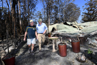 Property owner Stuart Skeen walks with Prime Minister Scott Morrison through his burnt-out property at Binna Burra in the Gold Coast Hinterland on Friday, September 13, 2019.