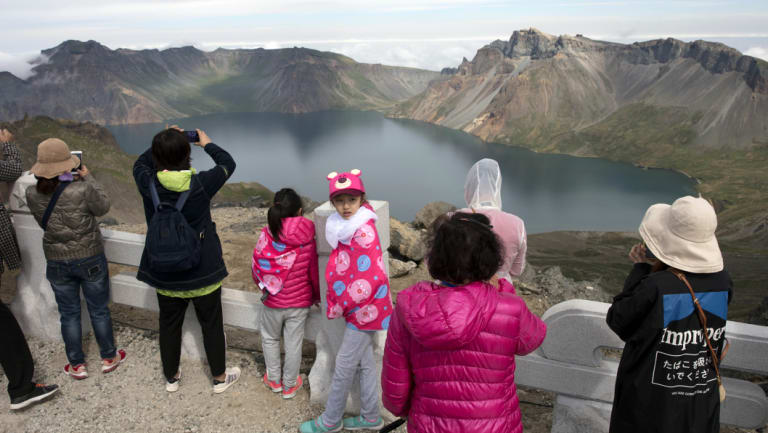 Chinese tourists take in the sight from a viewing platform overlooking the caldera of Mount Paektu near Samjiyon in North Korea.