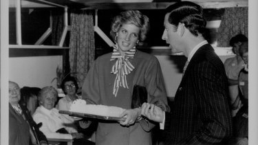 "Prince Charles and Diana in London. The Princess was given a cake and joked with Prince Charles as she asked, ""Is there rum in it?""."