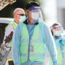 Biosecurity and airport staff in PPE and masks are seen around the chartered flight QR7176 after it arrived in Melbourne carrying Australian Open players.
