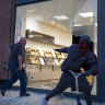 A store is damaged in the Chelsea neighborhood of New York as looters grabbed merchandise along the street