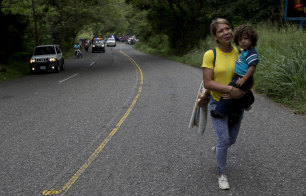 Honduran migrant Mary Dominguez carries her two-year-old son Dominic into Esquipulas in Guatemala on Tuesday.