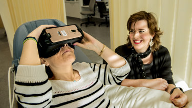 Prince of Wales Hospital is trialing VR therapy to help patients recover. Pictured is Theodora Michalopoulos wearing a VR headset while former patient Stefanie Ammann looking on.