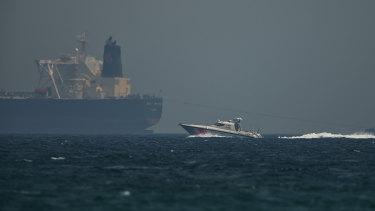 An Emirati coast guard vessel passes an oil tanker off the coast of Fujairah, United Arab Emirates.