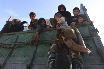 A baby is lifted onto a truck carrying civilians fleeing Maaret al-Numan, Syria, last week, ahead of the government offensive.
