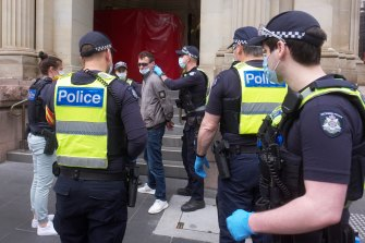 A man is detained by police in Melbourne on Friday.