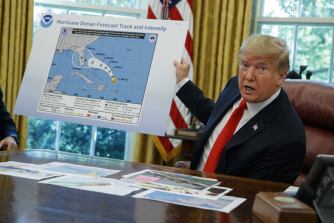 President Donald Trump shows a map forecasting the path of Hurricane Dorian.