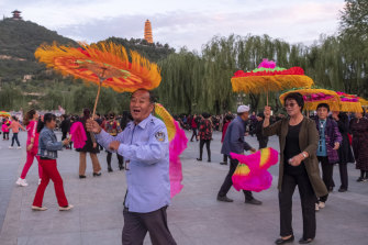 Yan'an locals enjoy square dancing, or plaza dancing, in the shadow of the town's Pagoda Hill.