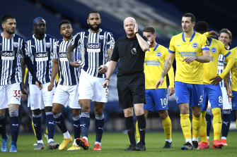 West Brom and Brighton players gather around referee Lee Mason as he makes the decision on whether to allow a goal to stand.