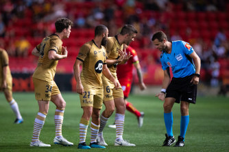 Referee Chris Beath explains to Western Sydney players why he gave Adelaide's first penalty.