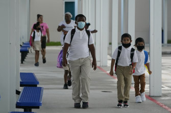 Children arrive for the first day of school on August 10 at Washington Elementary School in Florida, where schools have defied the Governor to mandate masks.