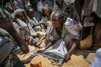 An Ethiopian woman argues with others over the allocation of yellow split peas after it was distributed by the Relief Society of Tigray in the town of Agula.