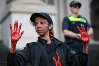 Aboriginal and Torres Strait Islanders communities and allies with their hands painted red march during a protest in Melbourne last year following the death of 19-year-old Warlpiri teenager Kumanjayi Walker.