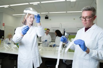 Luke Gordon and Ben George in the Sydney University X-Lab with laser-cut face shields designed for use in hospitals, with APPEAR team members in the background.