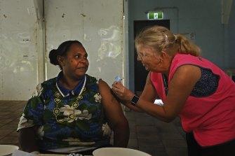 Norah Tabuai receives her second AstraZeneca COVID-19 vaccination on Saibai Island from a Queensland Health nurse.