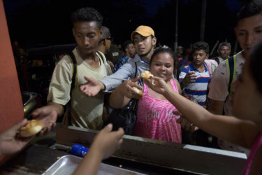 Migrants receive bread from residents in Esquipulas, Guatemala as they make their way to Mexico and the US.