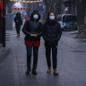 Chinese women walk in a usually busy shopping and tourist area during the Chinese New Year holiday in Beijing, China.
