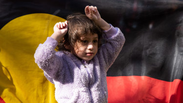 A young girl puts her fists up in the air in a sign of protest.