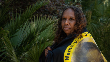 Bernadette Clarke wrapped with an Aboriginal flag with her sister's photo.