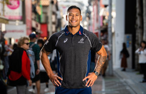 Star attraction: Folau poses for the cameras at a Wallabies fan event in the Harajuku district of downtown Tokyo.