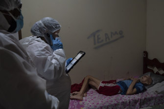"""Mobile Emergency Care Service (SAMU) worker Aline Moreira checks on an elderly COVID-19 patient at home before transferring him to a hospital in Duque de Caxias, Rio de Janeiro state, Brazil. On the wall, the message """"I love you""""."""