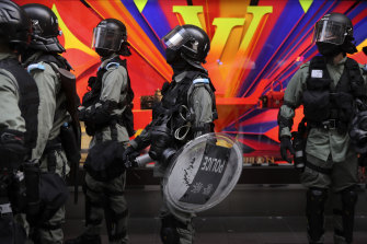 Riot police patrol near a Louis Vuitton store during a demonstration in Hong Kong's financial district.
