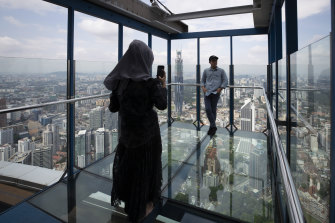 Tourists pose for photos at the Skybox in Kuala Lumpur. Malaysia has entered a 'Recovery Movement Control Order' after three months of coronavirus restrictions.