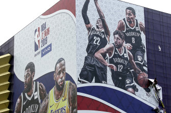 A billboard advertising an NBA preseason game between the Los Angeles Lakers and Brooklyn Nets in Shanghai.