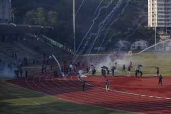 Students try to clear the tear gas canisters fired by riot police on the sports track during a confrontation in the Chinese University in Hong Kong.