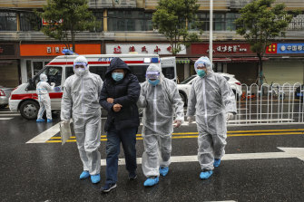 In Wuhan, on January 26, medical workers in protective gear help a patient from an ambulance.