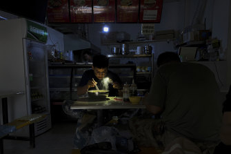 A man uses his smartphone to light up his breakfast during a blackout in Shenyang in north-eastern China.