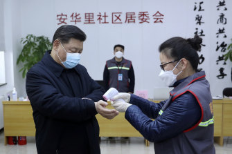 Chinese President Xi Jinping, pictured left in a face mask, has his temperature taken.