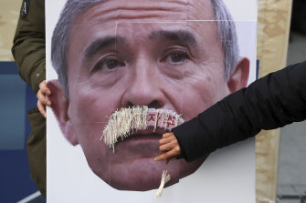 A protester plucks a fake moustache from a picture of the US ambassador to South Korea, Harry Harris.