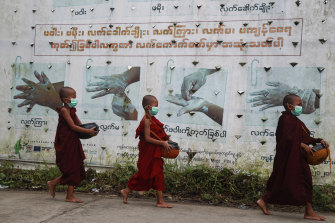 Buddhist novice monks wearing face masks walk past a COVID-19 awareness sign as they collect morning alms in Yangon on Thursday.