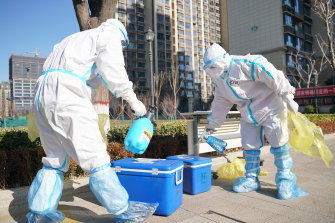 Workers disinfect containers of coronavirus test samples outside a residential complex in Shijiazhuang in northern China's Hebei Province on Friday.
