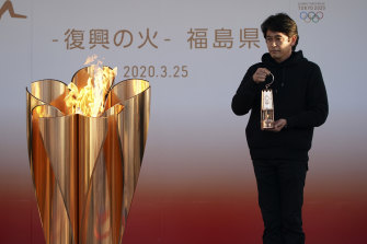 Keepers of the flame: an official holds a lantern containing the Olympic Flame  in Iwaki, northern Japan, on Wednesday.
