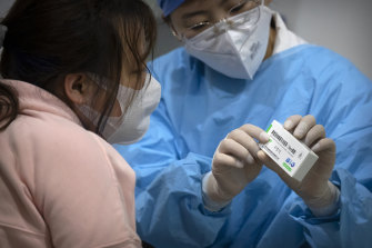A medical worker shows a person the packaging for a Sinopharm vaccine at a vaccination facility in Beijing. Some countries have seen a rise in COVID cases after two doses of the vaccine and are recommending a third shot of a different vaccine.
