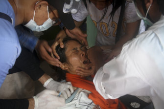 A woman is treated by a nurse after being tear-gassed during an anti-coup protest in Yangon on Tuesday.