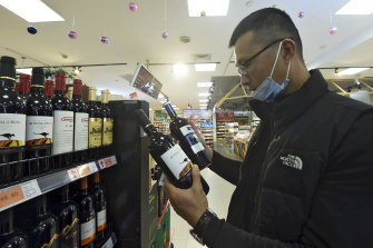 A man compares two bottles of Australian wine at a supermarket in Hangzhou in east China's Zhejiang province.