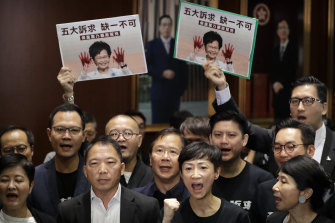 Pro-democracy legislators wave placards showing Carrie Lam with blood on her hands.