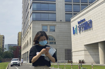 A woman checks her phone outside the headquarters of TikTok owner ByteDance in Beijing.