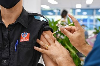 An emergency worker receives a COVID-19 vaccine at the new mass vaccination hub at Sydney's Olympic Park.