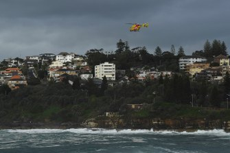 A helicopter searches along the coastline for a surfer who went missing at Coogee Beach yesterday.